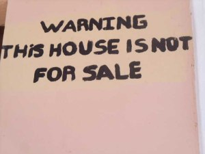 "A ""not for sale"" sign on a house near Lake Cocibalco"